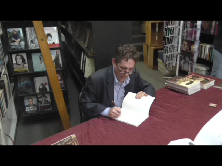 Michael Christaldi signing books for fans.